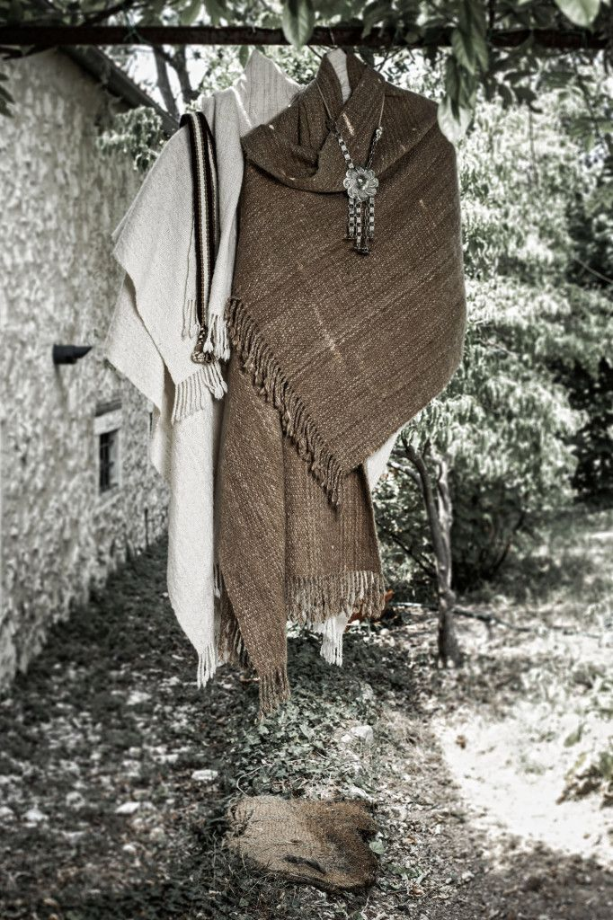 """White and brown Portal ruana wraps: 100% fine llama's wool hand spun and woven by loom - ecru and brown wool has the natural color without dyeing - finished with a twisted fringe Rastra necklace: silver 925 - intertwined leather strings - """"Rastra"""": traditional metal ornament on gaucho's belt"""