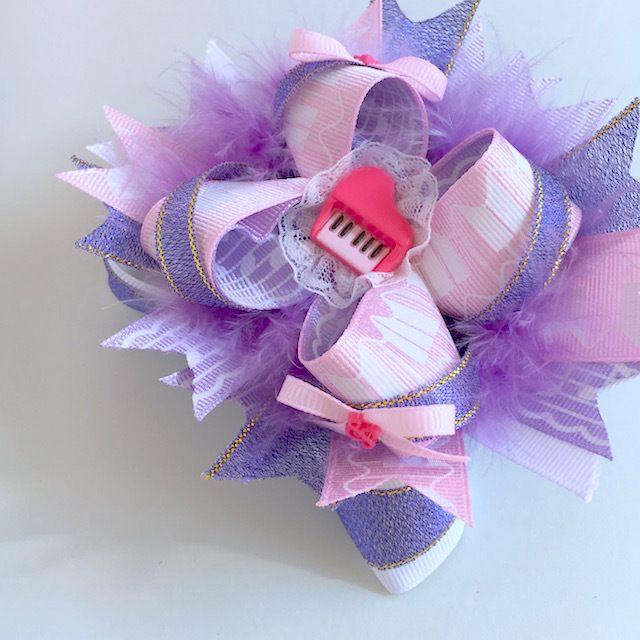 センターのピアノパーツ、ピンクの鍵盤柄×紫の楽譜柄のリボンで、ピアノの発表会をイメージしたカチューシャです。対角線上に付けたミニリボンのセンターにも小さなト音記号。ふわふわフェザーとたっぷりのリボンでボリューム満点のカチューシャです。ピアノの発表会やレッ...