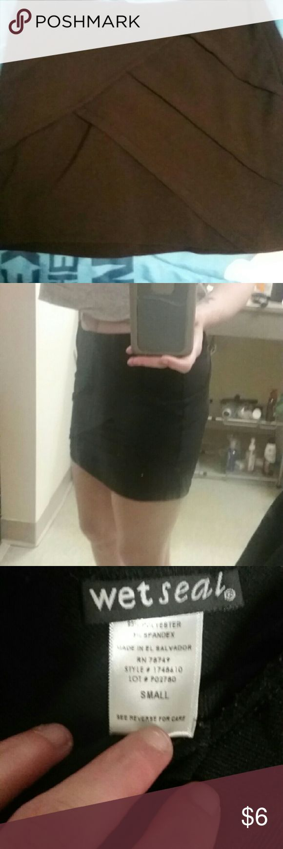 Black skirt Black, short skirt with a  texture of lines going in different directions, tight fitting and not worn many times Wet Seal Skirts