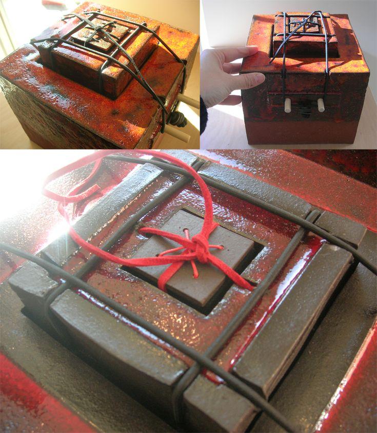 MIJMERDOZEN:   Mijmerdozen is een groeiende serie keramische dozen waar diverse persoonlijke objecten in bewaard kunnen worden. De dozen bestaan uit verschillende lagen/onderdelen (doos in doos in doos). Eén van de lagen is b.v. een bundel, waarin fotootjes, briefjes of haarlokjes bewaard kunnen worden.De bundel kan als ketting gedragen worden of in het bovenste doosje bewaard worden.