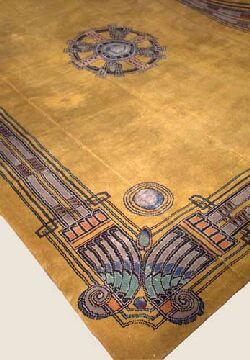 Art Deco Egyptianesque carpet,  machine woven, the golden yellow field with central medallion and polychrome motifs to the corners, 449cm x 332cm, Sold for £1,058