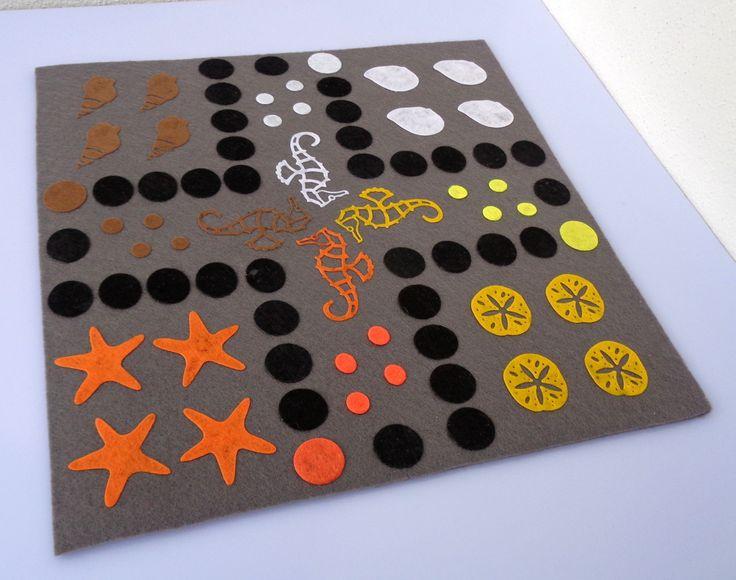 Člověče,+nezlob+se+-+mořské+Velmi+oblíbená+hra+vyrobena+z+filcu,+základ+je+z+3mm+plsti,+na+něm+jsou+připevněny+filcové+aplikace.+Herní+deska+je+velká+27x27+cm.+Hra+obsahuje+4ks+plastových+pajduláků+z+každé+barvy+z+herní+desky+(16+ks)+a+2ks+bílých+kostek+dodávané+v+pytlíčku.
