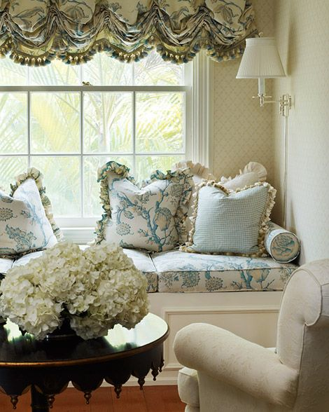 The same floral fabric used for the master bedroom's canopy bed appears here on window-seat cushions and a balloon shade edged with silk-tassel trim. Two armchairs and a whimsical black-painted table face the window seat, which is softened by ruffle-trimmed pillows.