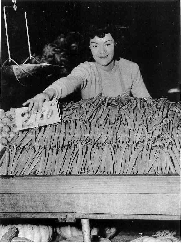 Mary Mow at Prahran Market, selling beans at Prahran Market. Mary is the daughter of Mr Daniel Wong Mow, a Canonese dentist who migrated to Melbourne and practised in Lonsdale Street. Prahran Council is said to have asked him in the early 1890s to encourage Chinese friends to set up produce stalls at Prahran Market. Daniel married an Australian woman and had 8 children - 4 boys and 4 girls. The Mow market stall in 1998 is a third generation stall, specialising in potatoes.