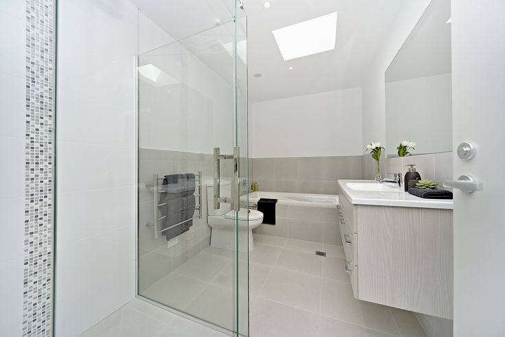 The white tiles in this bathroom create a spacious atmosphere, offset by the modern glass-tiled feature in the shower