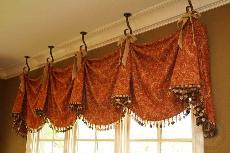 Something like this w/o hooks but mounted on cornis board.  Look for right shade of red/rust/maroon to carry color tones from livingroom thru to bedroom.