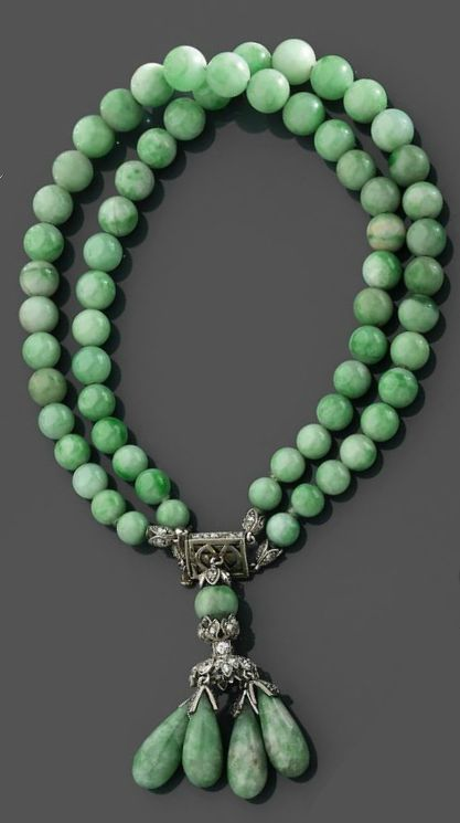 An Art Deco jadeite and diamond bracelet, circa 1920. Consisting of two rows of green jadeite spheres, with a clasp set with rose-cut diamonds, suspending four pear-shaped jadeite drops, mounted in platinum and white gold. #ArtDeco #bracelet