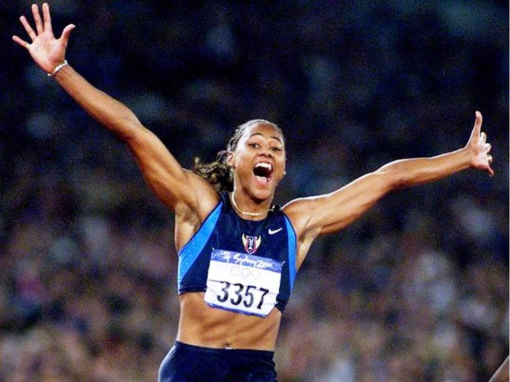 Athlete Marion Jones of USA crosses the finish line with outstretched arms after winning 100 sprint final of Sydney 2000 Olympic Games at Stadium Australia, Homebush. She was later stripped of the medal in 2007 when she admitted to doping