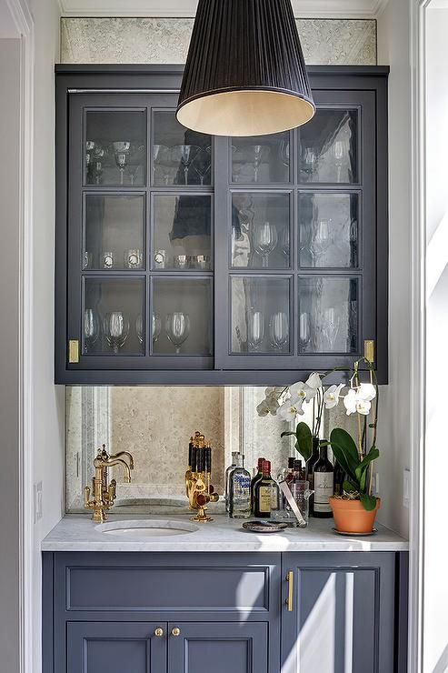 This gorgeous dark gray wet bar boasts sliding glass dark gray cabinets fitted with brass inset hardware and mounted to an antique mirrored backsplash.