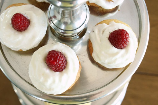 """Victorian Sponge Cake: In America, we call them cupcakes, but in England, """"small cakes"""" are served during tea. This Victorian sponge cake is made with a simple ratio: equal weights of sugar, flour, egg, and butter. The dainty sponge cakes are then topped with whipped cream and a fresh berry for a picture-perfect treat."""