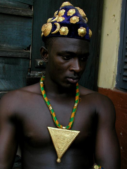 Africa | An 'Abotire' crown of gold leaf pieces from the ASHANTI people of the IVORY COAST |  Its name in the Akan language is abotire. This is the oldest, most traditional of crown styles, worn by all levels of Ashanti royalty.| The pendant is gold leaf-covered wood, also from the Ashanti people of the Ivory Coast.