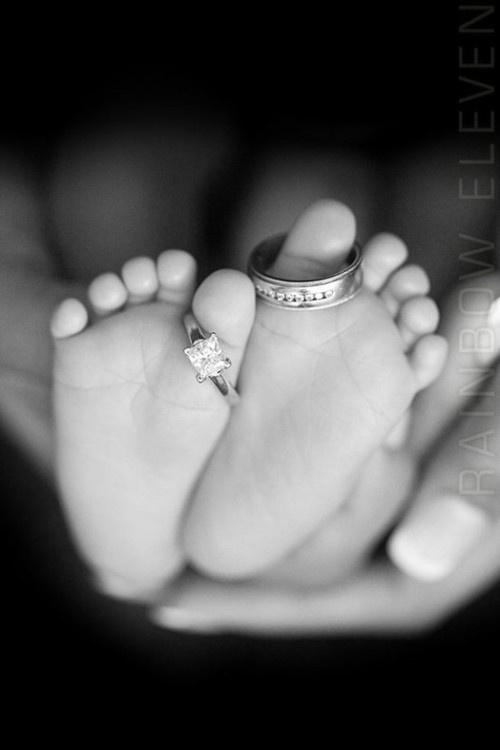 Baby feet with wedding rings on toes