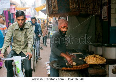 VARANASI, INDIA - JAN 4: Asian cyclist rides on a narrow indian street by street vendor of traditional cake bread on January 4, 2013. Varanasi urban agglomeration had a population of 1,435,113