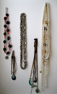 Use nails to hang necklaces. Paint the nail heads with nail polish to make it more like a display.