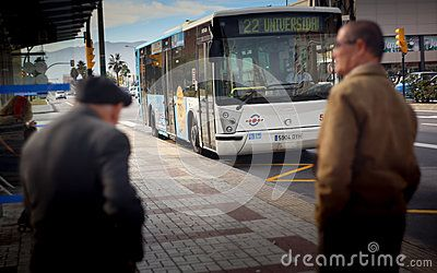 Two old men waiting the bus. Malaga city in december.  Line 22.