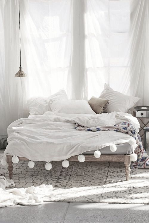 A white cloud of a bedroom. We love the pom poms on that bed throw.