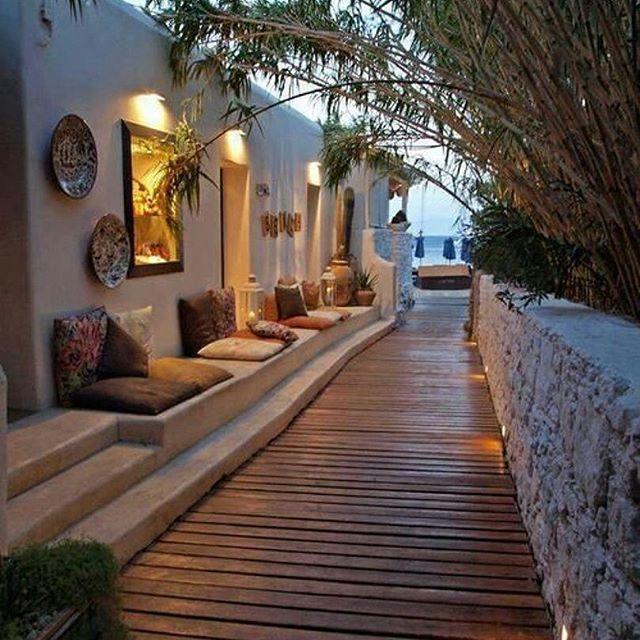Varanda com piso em madeira, bancos em concreto feito nos degraus e com almofadas nos acentos e encosto, iluminação indireta amarela e pratos nas paredes brancas.