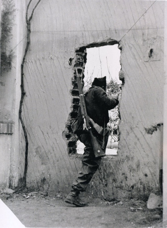 Gerda Taro Republican soldier stepping through a hole in a wall, University City, Madrid, February 1937