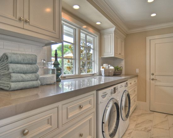 Long and narrow laundry room. Love the counter and the window!