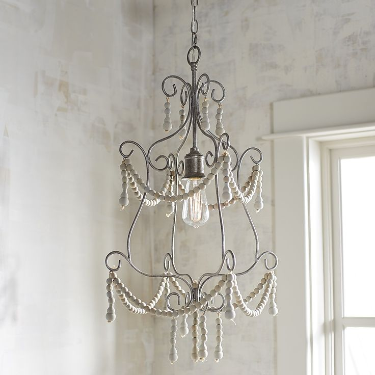 Our Mame chandelier is a charming mademoiselle that features wooden beads painted antique white and draped on a pewter-toned iron frame. This vintage-style, tiered fixture can inhabit a variety of settings—from a shabby-chic dining room to a modern farmhouse entryway.