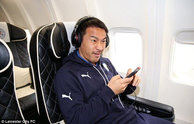Shinji Okazaki pulls a face as he plays on his phone prior to take-off from East Midlands Airport
