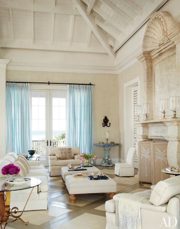 Architect Clemens Bruns Schaub designed Hilary and Galen Weston's Windsor, Florida, house; John Stefanidis handled the decor. Candy-striped tulle curtains brighten the living room, where a monumental fireplace and overmantel of carved Mexican shell stone fills a wall; the seating and embroidered fire screen are by Stefanidis. | archdigest.com