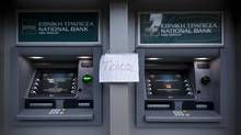 A handmade sign that reads End sits taped between automated teller machines (ATM) outside a National Bank of Greece SA bank branch in Thessaloniki, Greece, on Saturday, June 27, 2015. Greek Finance Minister Yanis Varoufakis faces questions from his euro-area counterparts after the decision to call a referendum on the terms of Greece's bailout upended work to resolve a standoff over aid. (Konstantinos Tsakalidis/Bloomberg)