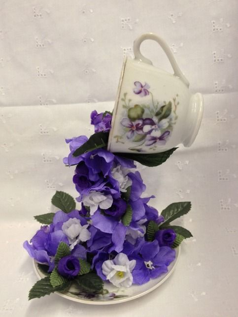 """Small floating cup and saucer floral arrangement. It stands 7"""" high and 4 1/2"""" across at base. Cup has beautiful purple florals cascading down to it's matching saucer. This item is made by a local vendor of the DIY Craft Boutique."""