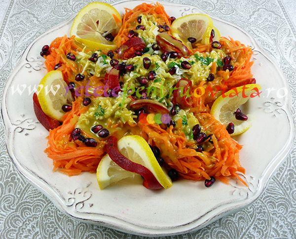#Reteta de salata de varza cu morcovi si dressing de lamaie, portocala, ulei de masline si mustar, ornata cu ardei capia, felii de lamaie, patrunjel si seminte de rodii.