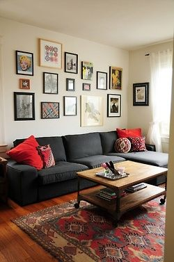 Red and gray? printed carpet, red accents, dark grey couch, wall of frames, gallery, industrial rustic coffee table.