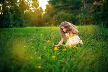 Девочка срывает цветок в парке