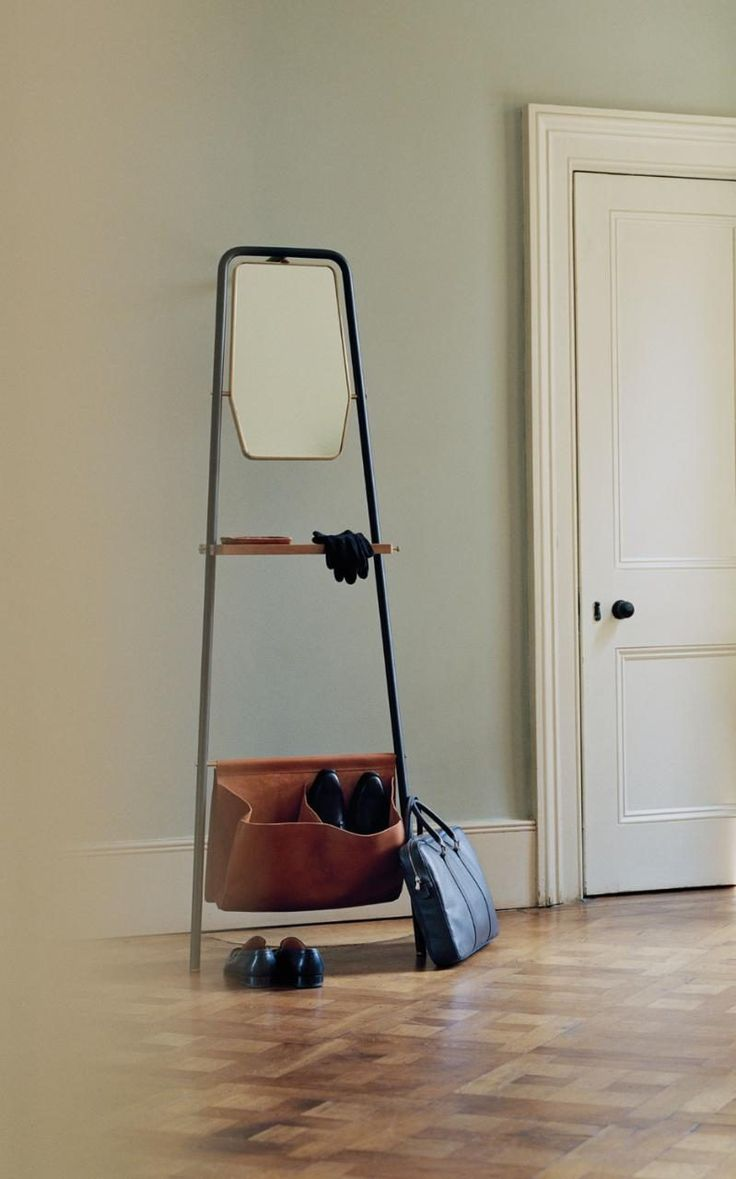 The Valet incorporating a walnut wood shelf, a leather bag, brass hooks and hexagonal mirror on adjustable leather strap, by David Rockwell for Stellar Works.