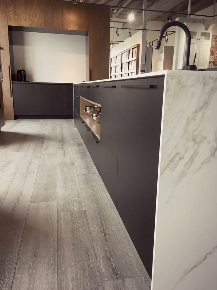 A modern style black kitchen with a marble-style dekton counter. Une cuisine noir de style moderne avec un comptoir de dekton style marbre.
