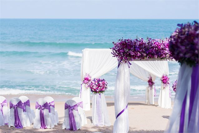 Purple themed decor for a wedding on the beach.