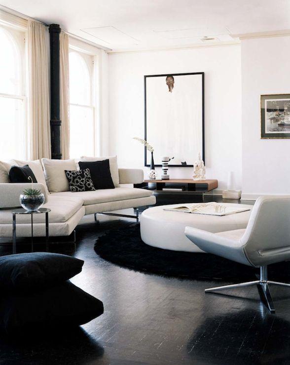 Modern white & black living room design with white modern sectional sofa, black pillows, glossy ebony wood floors, round white leather ottoman, black velvet floor cushions, round black flokati rug and white leather modern chair. TT
