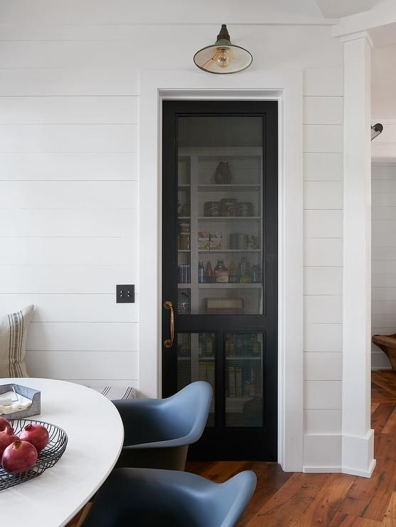 Cottage kitchen boasts a shiplap wall fitted with a black mesh screen door fitted with an antique brass door handle illuminated by a vintage barn sconce.
