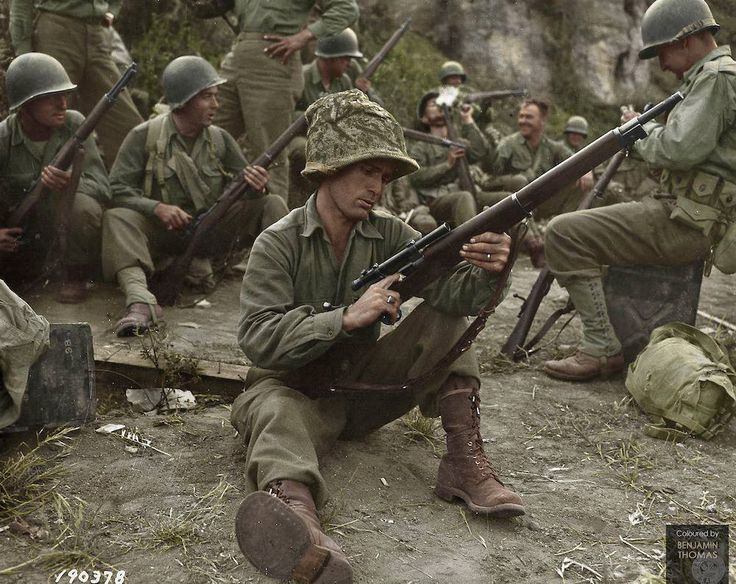 In the foreground is U.S. sniper Pfc. Edward J. Foley, Co 'G', 143rd Infantry, 36th Infantry Division cleaning his Springfield 1903A4 rifle, Near Velletri, Lazio, Italy.