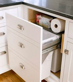 Hidden Assets A pullout fronted by a panel that resembles three drawer fronts conceals multiple receptacles. Accommodate cleanup tools and extra trashcan liners by including a storage shelf above the bin