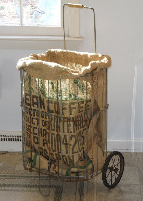 """""""take a vintage shopping cart, put a burlap coffee sack in it, turn the unfinished edge under to form a cuff and fit it around the perimeter, and put a plastic garbage can in it to protect the coffee sack"""""""