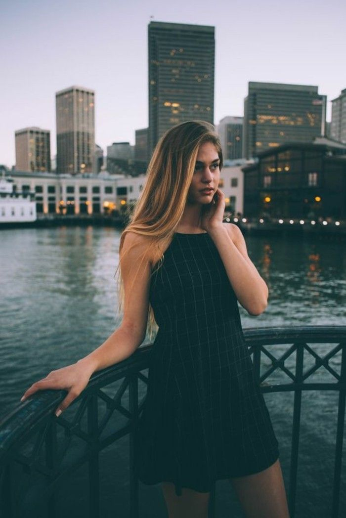 casual dress code, young woman with ombre blond hair, wearing black sleeveless mini dress, with subtle checkered pattern, leaning on black metal railing over water