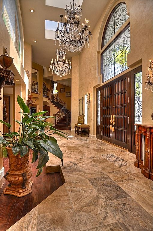 Massive grand entrance that is two stories in height.  Half-landing stair case is far off to the right of the entry hall.  Large arched window above the front door along with skylights in the hall flood the space with light.