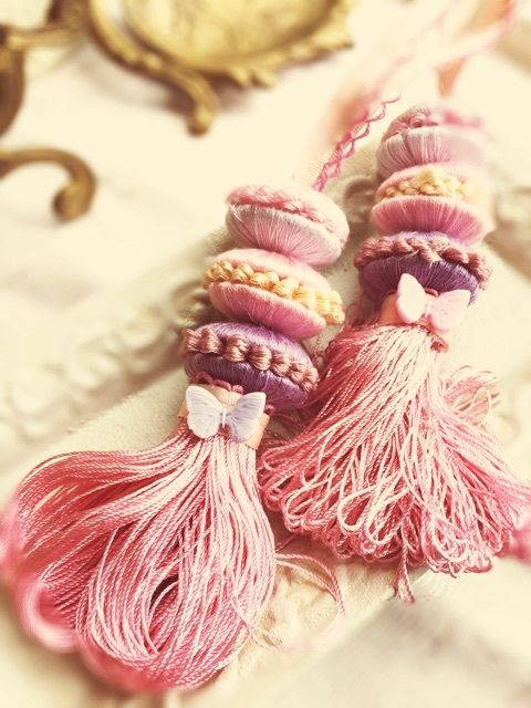 A sweet little butterfly has landed on each of these tassels.