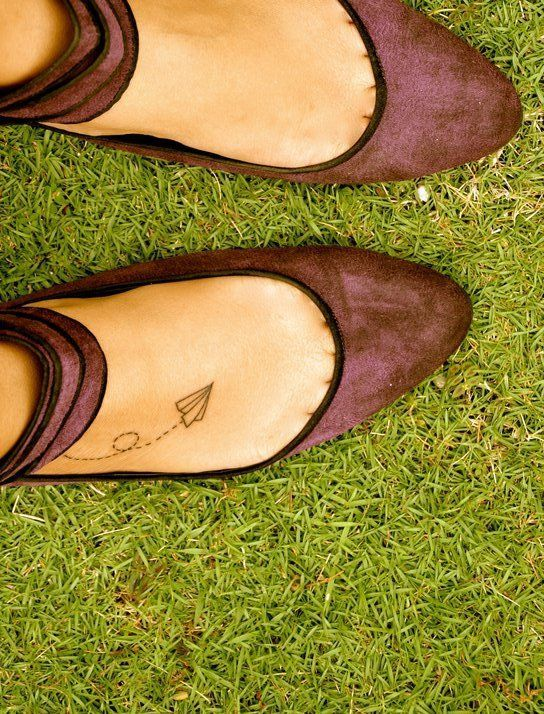 """paper airplane tattoo on right foot, """"it is finished"""" small cursive in same place on left foot"""