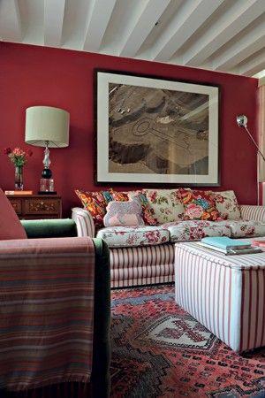 Estampas e cores em profusão Nesta saleta de TV, a designer de interiores Neza Cesar revestiu a estrutura do sofá com sarja listrada – a mesma do pufe – e os almofadões com o tecido florido. A poltrona recebeu veludo verde-oliva, tudo feito pela Tapeçaria Monelli. As cores intensas do tapete persa estampado inspiraram a pintura da parede na cor vermelha e outros detalhes da decoração, como a almofada com formato de gato rosa e turquesa.  (Foto: Edu Castello e Marcelo Magnani)