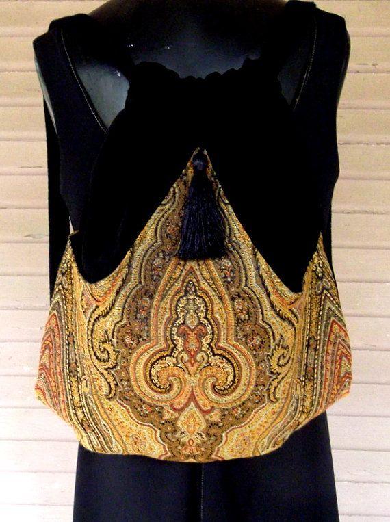 Original sac à dos à la main faite de velours noir. La poche extérieure est une tapisserie de médailles dor avec une touche de rouge brique et indiqué en noir. Il arches dans le milieu et cousu au point. Cette poche extérieure est bordée de satin. Le sac lui-même est surfilé à lintérieur et mesure 14 « x 18 ». Le gland est noir. Ce sac à dos est idéal avec celui à lextérieur de la poche pour ranger votre eau ou votre livre. Le rend idéal pour sur les filles vont.