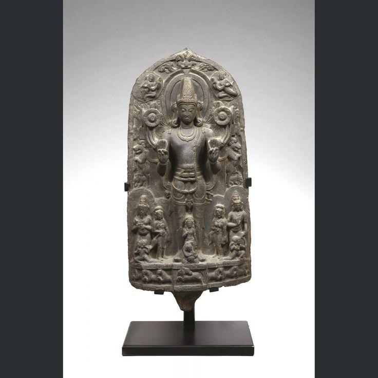 INDE - Epoque PALA Sena, XIIe/XIIIe siècle Grande stèle en basalte noir à décor sculpté de Surya debout sur un socle tiré par ses sept chevaux, les mains en abhaya mudra (geste de la non crainte) tenant des tiges de lotus. Il porte une coiffe tronconique et il est paré de boucles. Il est accompagné de deux couples. Dim. 78 x 37 cm.