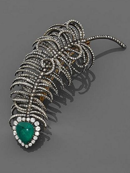 An emerald, diamond, silver and gold brooch designed as a trembleuse feather cabochon pear shape emerald in a circle of brilliant-cut diamonds, supported by a stem set with rose cut diamonds. Frame in 14K rose gold and silver, 18K gold pins.  Circa 1890.