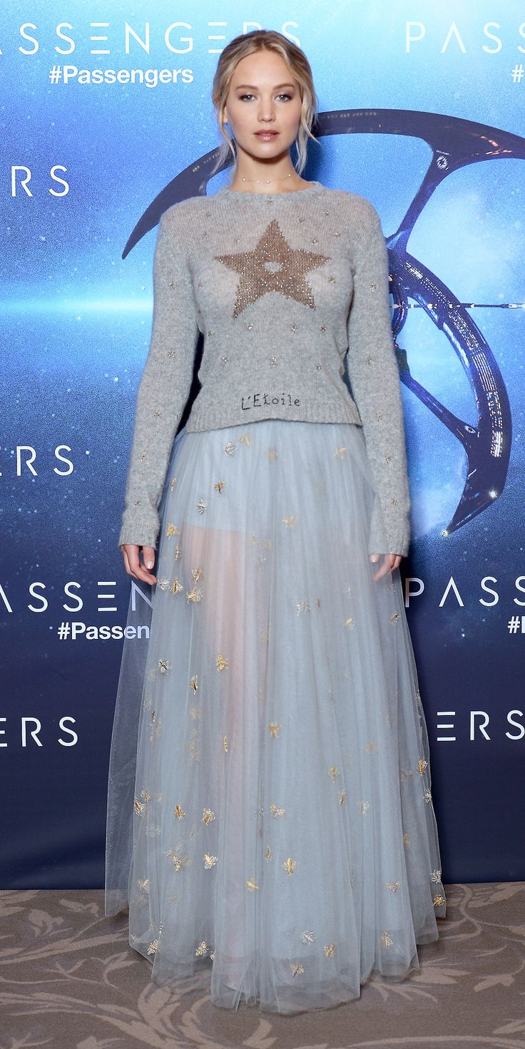 "For the Passengers photocall Jennifer Lawrence wore an outfit, courtesy of Dior, that was out of this world. She packed on the whimsy with a star intarsia knit (with the word star in ""French"") and an airy pale blue tulle evening skirt, complete with the daintiest gold chain choker."