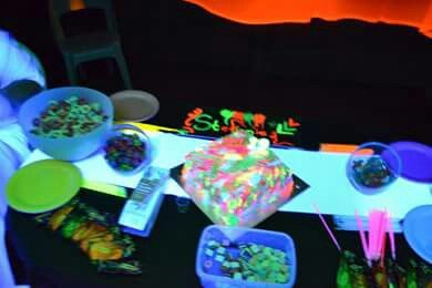Snacks like sour worms gloe in the dark lollipops and liqourice and sugarpuffs with bright paper plates