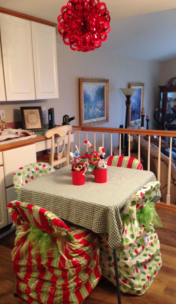Kids' Table - treat buckets, foil pendant overhead, plastic toy bag chair covers tied with a green sparkly tulle bows.  The only things missing are a large bowl of black olives and a bowl of candy!  I have four grand babies 4 & younger - hope they come to ❤️ this year after year!